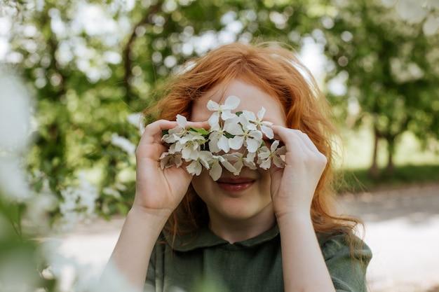 Uma garota de cabelo vermelho cobriu os olhos com flores de maçã.