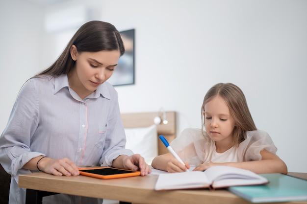 Uma garota de cabelos compridos estudando em casa e parecendo envolvida