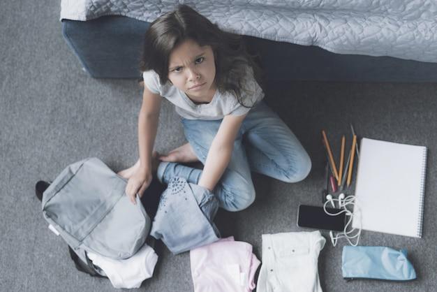 Uma garota de cabelos negros cercada por uma mochila cinza