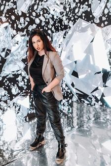 Uma garota de calça preta e uma jaqueta com um fundo de diamantes