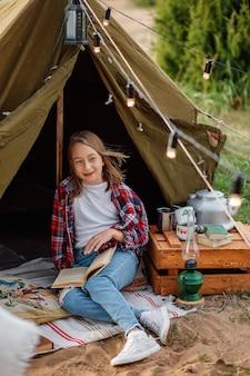Uma garota de camisa xadrez e calça jeans está lendo um livro ao lado da tenda.