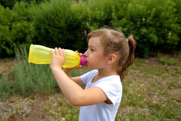 Uma garota de camiseta branca no verão na rua bebe água de uma garrafa de plástico amarela de qualidade ecológica.