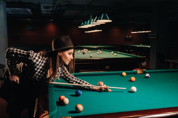 Uma garota de chapéu em um clube de bilhar com um taco nas mãos acerta uma bola