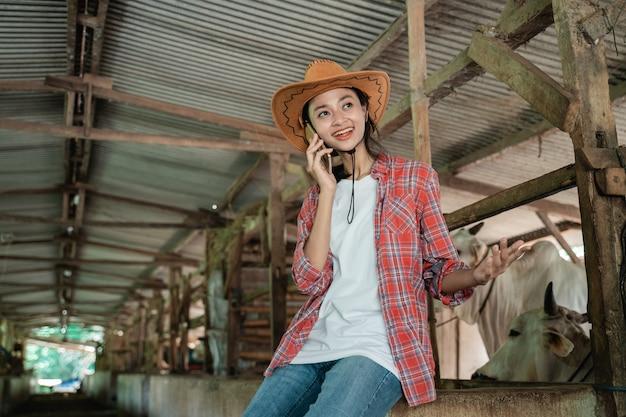 Uma garota de chapéu faz uma chamada usando um smartphone no fundo de uma cerca de madeira de uma fazenda de vacas