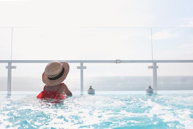 Uma garota de chapéu na piscina olha para o mar. fundo de verão com lugar para texto.