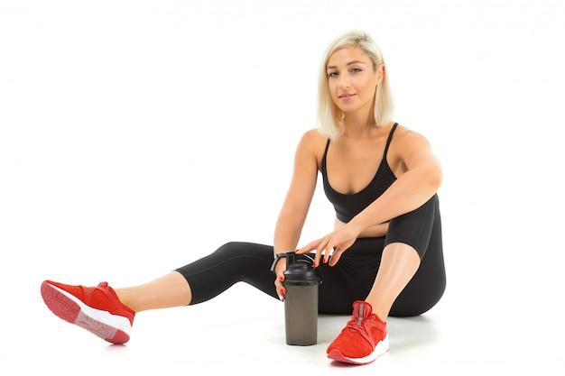 Uma garota de esportes com cabelos loiros e manicure brilhante em fones de ouvido, tópicos de esportes pretos, leggings e tênis vermelho segura uma garrafa de água de esportes.