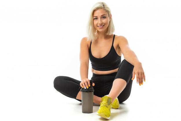 Uma garota de esportes com cabelos loiros e manicure brilhante em fones de ouvido, tópicos de esportes pretos, perneiras e tênis amarelo segura uma garrafa de água de esportes.