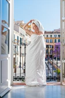 Uma garota de férias em um hotel, feliz inalando o ar pela varanda aberta
