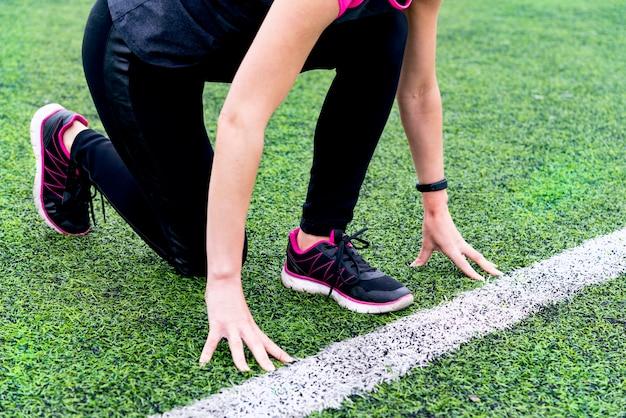 Uma garota de legging preta e um blazer rosa preparado para correr em uma esteira ao ar livre