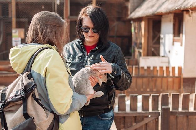 Uma garota de óculos escuros está acariciando um coelho, e a segunda garota o está segurando nos braços.