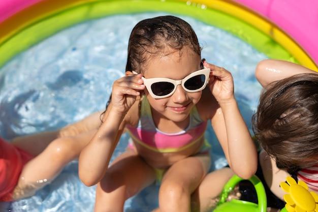Uma garota de óculos escuros está sentada em uma pequena piscina inflável com água limpa