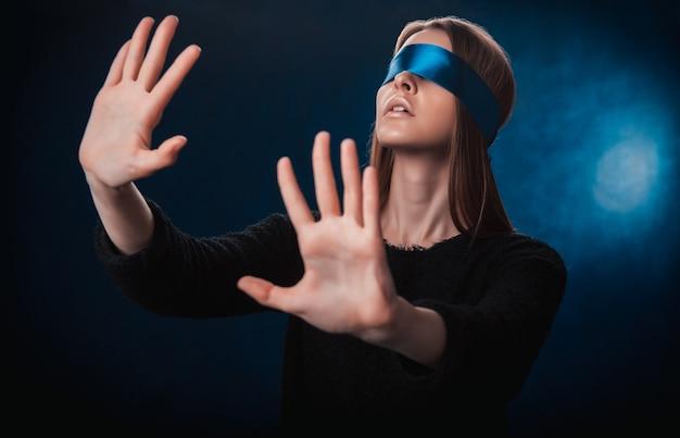 Uma garota de olhos vendados, com uma fita azul, procurando algo com as mãos, brincando, entretenimento, um enigma