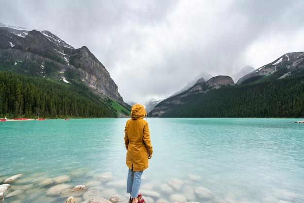 Uma garota de pé na frente do lago louise no canadá