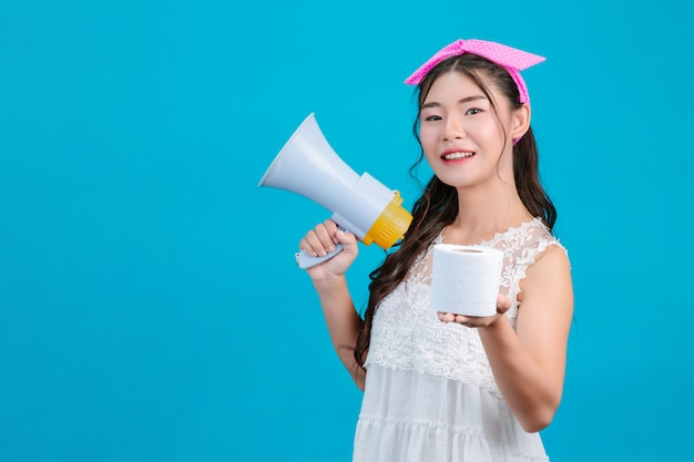 : uma garota de pijama branco segurando um megafone e segurando um lenço de papel na mão em um azul.