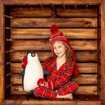 Uma garota de pijama de natal com um chapéu e luvas abraça um pinguim de pelúcia em um fundo de madeira