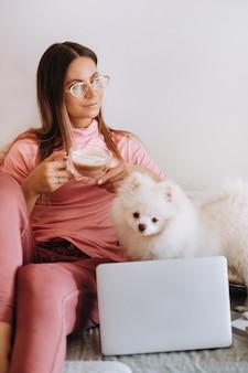 Uma garota de pijama em casa está trabalhando em um laptop com seu cachorro spitzer, o cachorro e seu dono estão descansando no sofá e assistindo o laptop.