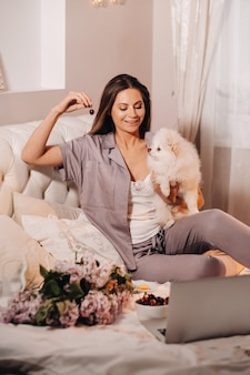 Uma garota de pijama se senta na cama à noite com seu cachorro branco, assistindo a um laptop e comendo doces. garota com um cachorro spitzer em casa na cama.
