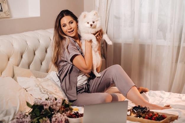 Uma garota de pijama sentada na cama à noite com seu cachorro branco