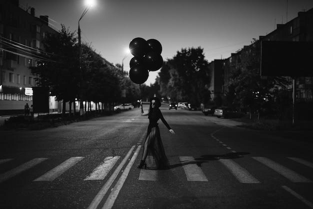 Uma garota de preto com balões nas mãos cruza a estrada