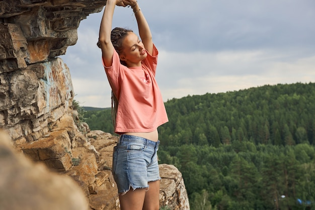 Uma garota de shorts curtos e uma camiseta rosa chega em pé perto de uma caverna no topo de uma montanha ...