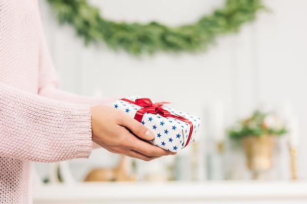 Uma garota de suéter rosa, tem nas mãos um presente com estrelas azuis e uma fita vermelha. sobre um fundo claro. conceito sobre o tema das férias.
