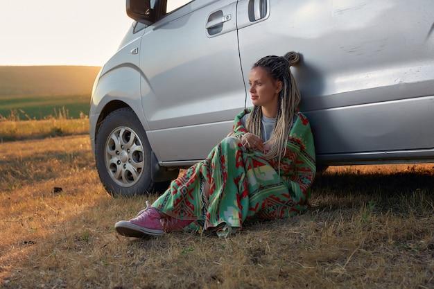 Uma garota de tênis rosa e um cobertor colorido está sentada perto de uma minivan contra o pano de fundo de um fi ...