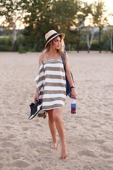 Uma garota de toalha e chapéu de palha está na praia com uma pasta de água e sapatos nas mãos