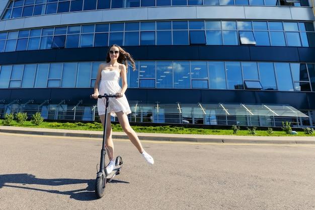 Uma garota de vestido anda de scooter elétrica perto de edifícios modernos