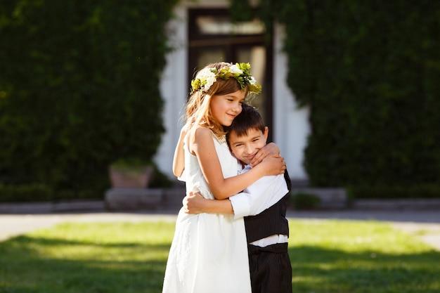 Uma garota de vestido branco abraça um garoto de terno elegante.