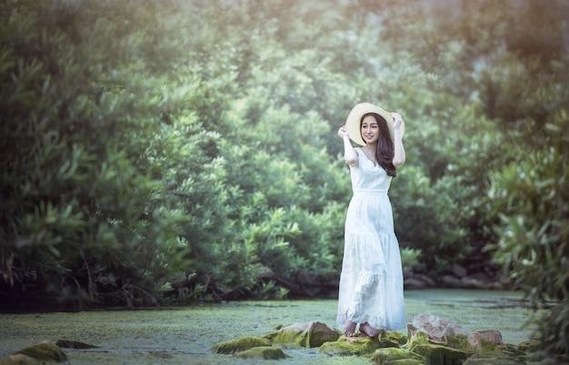 Uma garota de vestido branco fica na floresta.