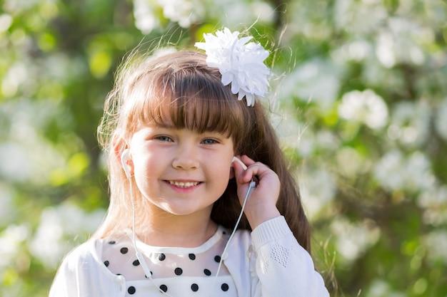 Uma garota de vestido branco ouve música através de pequenos fones de ouvido.
