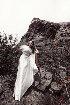 Uma garota de vestido branco pisca os pés descalços pisando em uma pedra, em meio a pedras