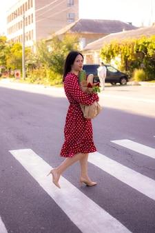 Uma garota de vestido desce a rua segurando uma sacola de papel com mantimentos nas mãos.