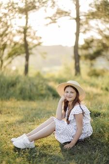 Uma garota de vestido e chapéu está no campo