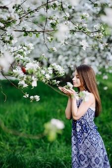 Uma garota de vestido longo azul aprecia o aroma de macieiras florescendo no jardim. jardim de florescência. temporada de alergia.