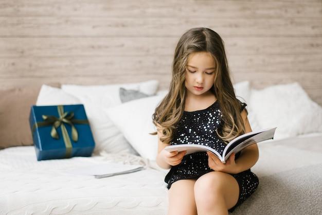 Uma garota de vestido preto está segurando uma revista e lendo-a, sentada na cama, sobre a qual está uma caixa de presente azul com um laço verde