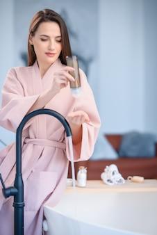 Uma garota de vestido rosa senta-se no banheiro e lisonjeia um gel de banho na mão