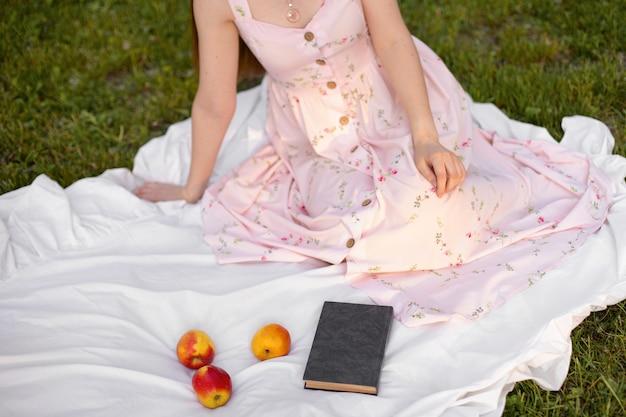 Uma garota de vestido sentada em um tapete no parque com um livro e maçãs