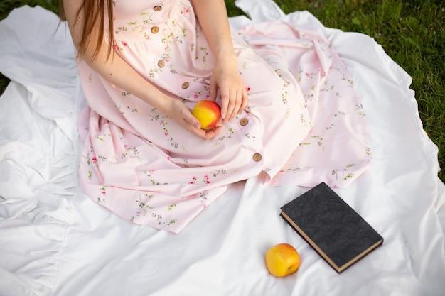 Uma garota de vestido sentada em um tapete no parque segurando uma maçã nas mãos