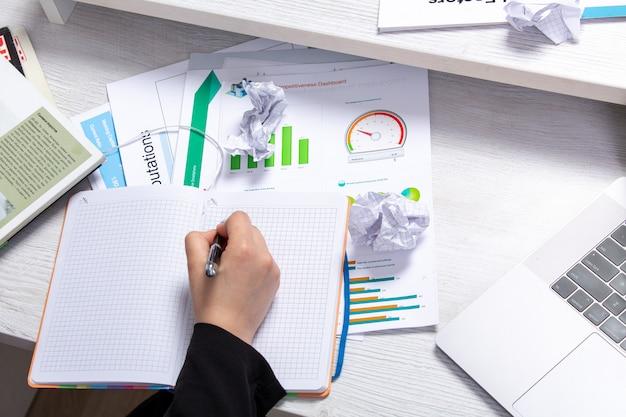 Uma garota de vista frontal tomando notas anotando notas na frente da mesa com agendas e gráficos e atividade de negócios de trabalho de laptop