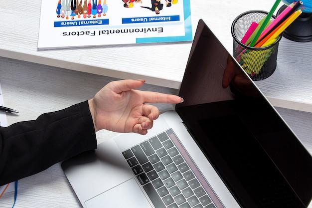 Uma garota de vista frontal usando o laptop na frente da mesa com agendas e gráficos e usando a atividade comercial de trabalho de laptop