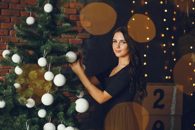 Uma garota decora uma árvore de natal