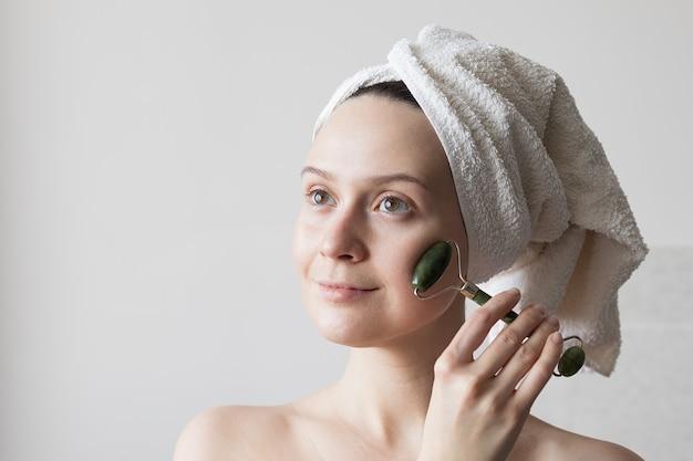 Uma garota depois do banho com uma toalha na cabeça faz uma massagem facial com um massagista de jade. foto de alta qualidade