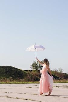 Uma garota descalça em um vestido de chiffon passeia sob um guarda-chuva branco