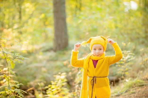 Uma garota divertida e divertida brinca e brinca em um passeio pela natureza