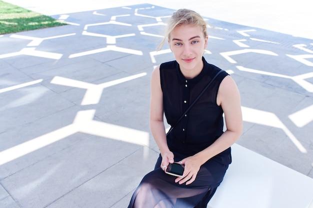 Uma garota do futuro senta-se no fundo de um edifício futurista, usa internet móvel 5g