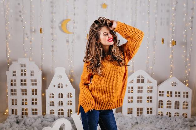 Uma garota doce e feliz com batom brilhante e olhos lindos em pé sobre decorações brancas com figuras festivas em forma de estrelas
