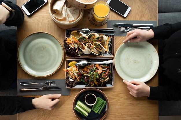 Uma garota e um cara à mesa estão jantando ou almoçando em um restaurante asiático. almoço no restaurante. pato à pequim e pratos apimentados.