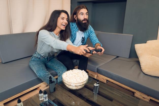 Uma garota e um cara jogam uma consola de jogos.