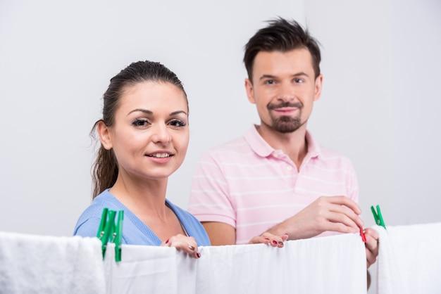 Uma garota e um cara penduram roupas para secar.